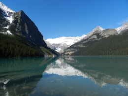 Classic view of Lake Louise and surround snow-capped mountains in front of the Chateau Lake Louise on a beautiful sunny morning in May , Amadeo P - August 2016