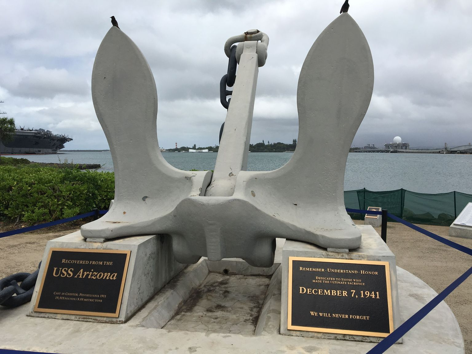 USS Arizonas anchor with the memorial in the background.