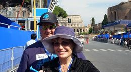 My husband and I, taken by Guide, on our way to the Forum ruins, prior to visiting Colosseum as seen in background. , Kerrin G - June 2015