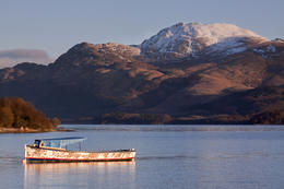 Boat on Loch Lomond, in dawn light, a snow-capped Ben Lomond behind - May 2011