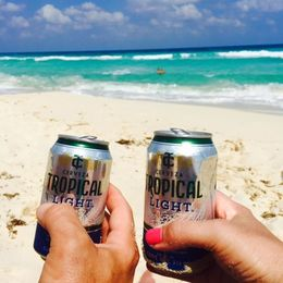Enjoying a tropical beer provided by the tour after playing in the surf , Donna R - April 2016