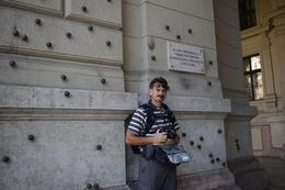My husband, Johann, standing infront of the wall of the building where you can still see the bullet holes of the attack in 1956., Elmarie Magda D - August 2010