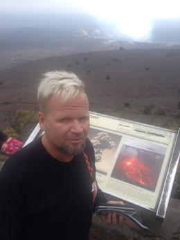 Henry Stonie reading about kilauea volcano crater rim while in the distance there is a steam coming out of the crater. , Lucho - January 2015
