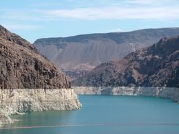 This is the view if you face the Lake Mead side of the Dam. Notice the water drop. The white represents the calcium deposits and gives you an idea of how much the water level has dropped over the ... , Gerald F M - July 2009