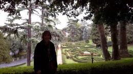 Carolyn standing in front of a beautiful landscaped garden area , Gene S - October 2013