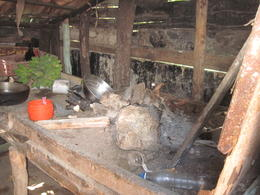 This is the cook stove built up on 2X4's with sand piled on top. they make their fire on the sand. Hen in basket on far back corner and green banana's....typical for the area. We were told that..., Harold T - February 2014