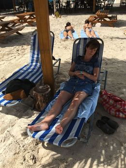 My wife napping in the shaded beach chair under one of the tiki-hut style covers , tnyankfan - July 2016
