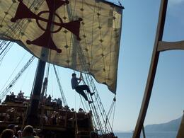 Crew member hoists the sail on the pirate ship , MARY L - June 2011