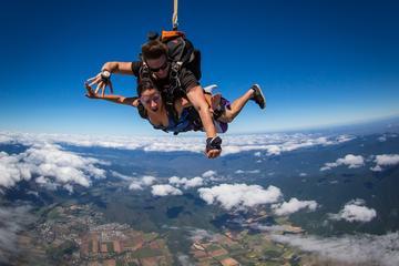 Salto en paracaídas en tándem en el arrecife y la selva tropical en...